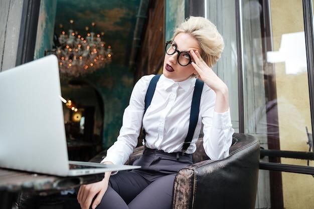Mooie jonge vermoeide blonde vrouw die met laptop buiten in café werkt