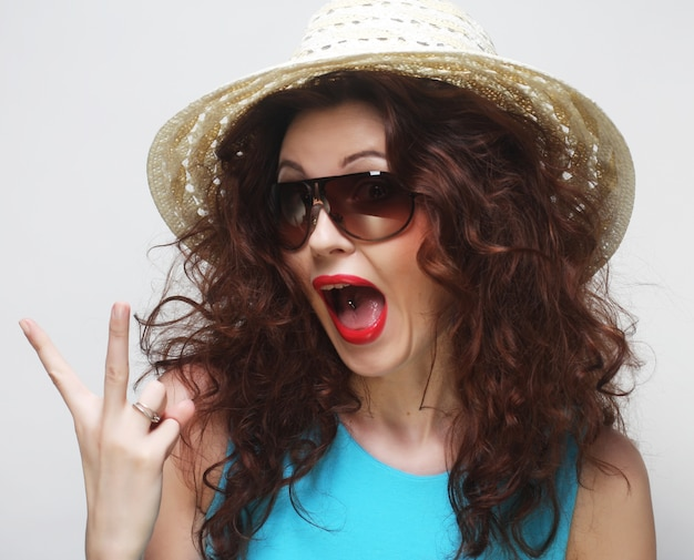 Mooie jonge verraste vrouw die hoed en zonnebril draagt
