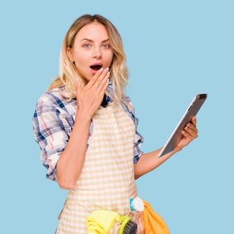 Mooie jonge verraste vrouw die schort draagt die digitale tablet houdt tegen blauwe achtergrond