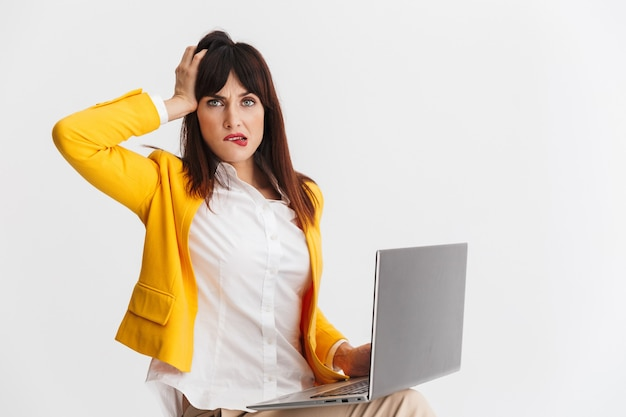 Mooie jonge verwarde zakenvrouw poseren geïsoleerd over witte muur met behulp van laptopcomputer.