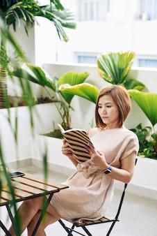 Mooie jonge vietnamese vrouw concentreerde zich op het lezen van een interessant boek terwijl ze aan de cafétafel zat