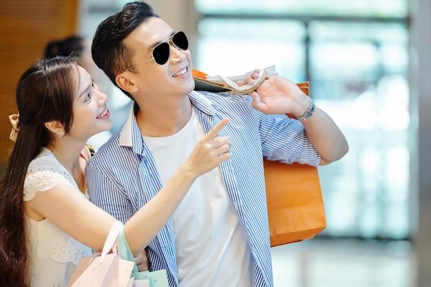 Mooie jonge vietnamese vrouw die naar de etalage wijst en een stijlvol kledingstuk aan haar vriendje laat zien