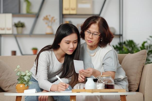 Mooie jonge vietnamese vrouw die rekeningen controleert en moeder helpt met de thuisboekhouding