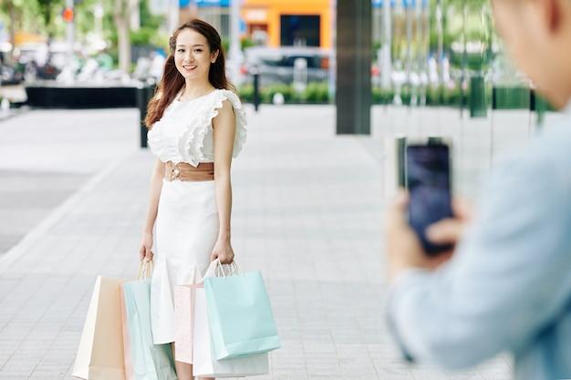 Mooie jonge vietnamese vrouw in witte jurk die vriendje vraagt om haar in de straat met boodschappentassen te fotograferen