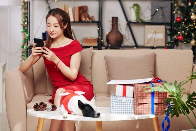 Mooie jonge vietnamese vrouw zittend op de bank met hondje in kerstkostuum en stapel cadeautjes op tafel voor haar en smartphone controleren