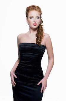 Mooie jonge volwassen sensuele vrouw in zwarte jurk poseren op witte muur