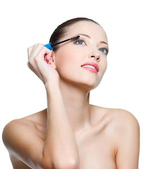 Mooie jonge volwassen vrouw die mascara op wimpers toepast - die op wit wordt geïsoleerd