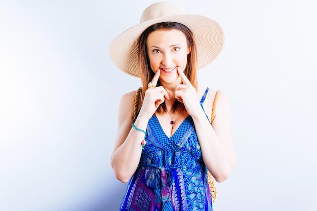 Mooie jonge volwassen vrouw die strandhoed en kleding draagt die met glimlach naar haar gezicht wijzen. concept wees blij of wees positief. zomer concept