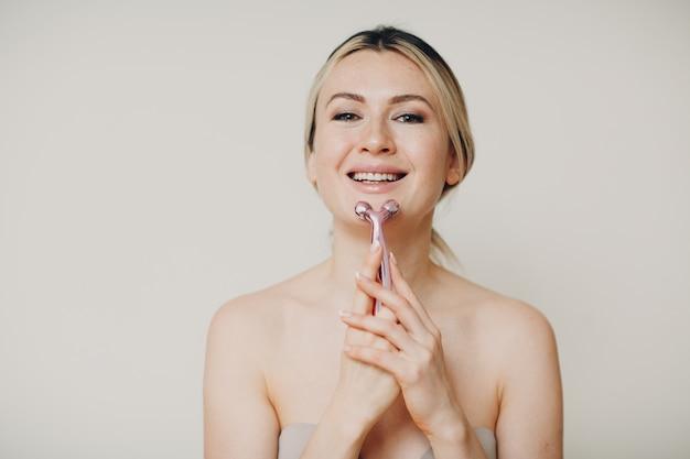Mooie jonge volwassen vrouw en massage gezicht roller op beige achtergrond