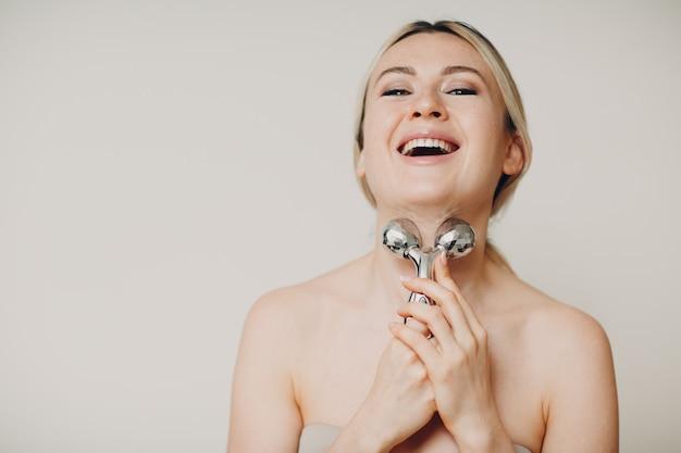 Mooie jonge volwassen vrouw en massagegezichtsrol op beige muur