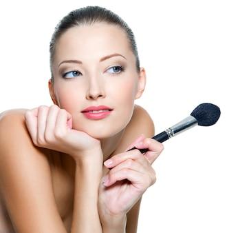 Mooie jonge volwassen vrouw houdt de make-up borstel voor het aanbrengen van rouge of poeder op wit wordt geïsoleerd