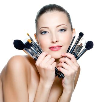Mooie jonge volwassen vrouw houdt de make-up borstels in de buurt van aantrekkelijk gezicht geïsoleerd op wit