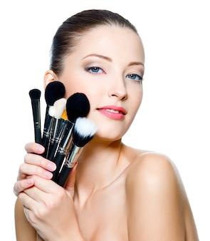 Mooie jonge volwassen vrouw houdt de make-up borstels in de buurt van aantrekkelijk gezicht. mannequin die zich voordeed op witte achtergrond