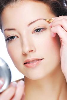 Mooie jonge volwassen vrouw in spiegel kijken en wenkbrauwen plukken