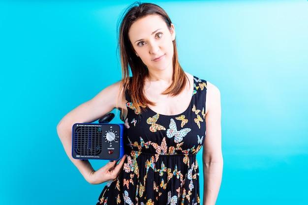 Mooie jonge volwassen vrouw in vlinder zomerjurk kijken ernaar uit met een ozonmachine. concept desinfectie van huis met ozon. vakantie. covid 19
