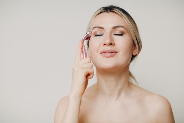 Mooie jonge volwassen vrouw met massage gezichtsroller op beige background