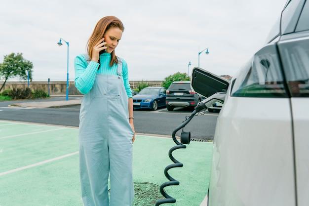 Mooie jonge volwassen vrouw praten op smartphone tijdens het opladen van elektrische auto bij oplaadstation