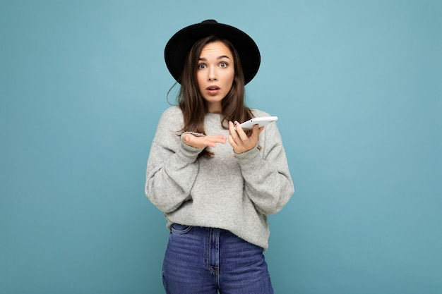 Mooie jonge vragen ontevreden brunette vrouw dragen zwarte hoed en grijze trui bedrijf smartphone kijken camera geïsoleerd op de achtergrond.