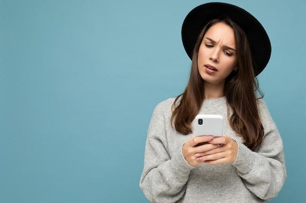 Mooie jonge vragen ontevreden brunette vrouw dragen zwarte hoed en grijze trui met smartphone naar beneden te kijken geïsoleerd op de achtergrond. kopieer ruimte