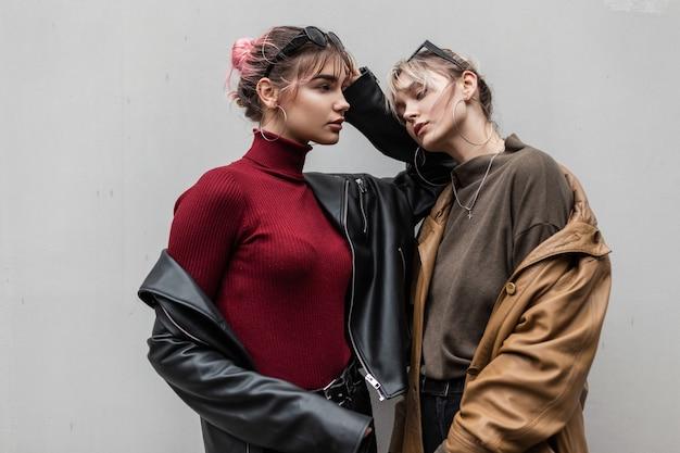 Mooie jonge vriendinnen meisjes in mode lente kleding met een leren jas en een trui staat op een grijze achtergrond