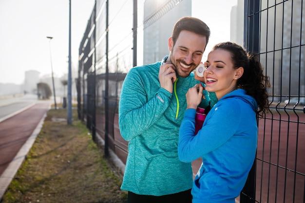 Mooie jonge vrolijke paar praten tijdens het rusten na training buiten