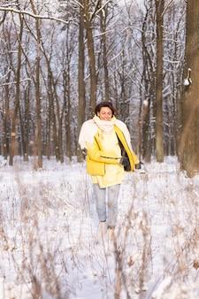 Mooie jonge vrolijke vrouw in een besneeuwd landschap winter woud plezier verheugt zich in de winter en sneeuw in warme kleren