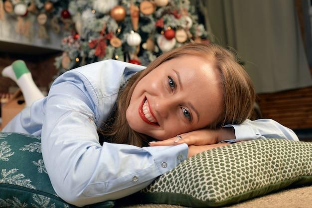 Mooie jonge vrouw aan de vooravond van kerstmis, ligt voor een open haard met een kerstboom en nieuwjaars decor en dromen. concept kerstwensen komen uit.