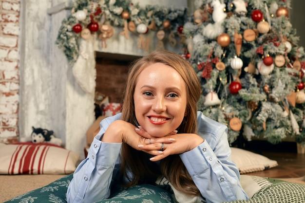 Mooie jonge vrouw aan de vooravond van kerstmis, ligt voor een open haard met een kerstboom en nieuwjaars decor en dromen. kerstwensen komen uit.