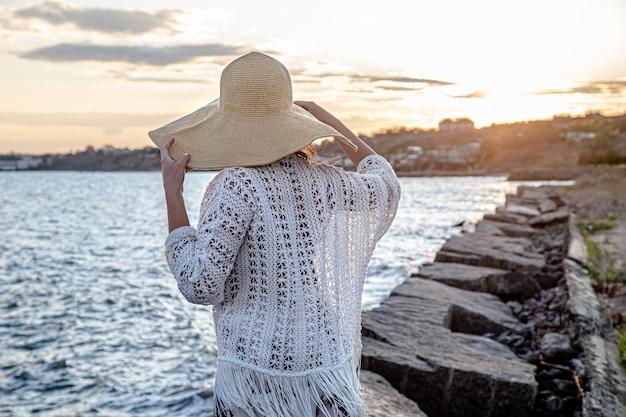 Mooie jonge vrouw aan zee bij zonsondergang. gekleed in een lange rok en hoed.