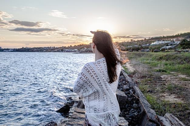 Mooie jonge vrouw aan zee bij zonsondergang.