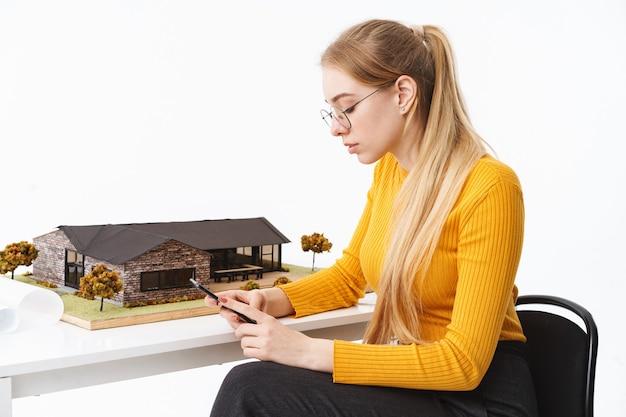 Mooie jonge vrouw architect zit aan de balie met huis model geïsoleerd over witte muur, met behulp van mobiele telefoon