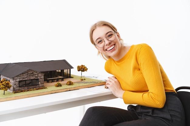 Mooie jonge vrouw architect zit aan de balie met huis model geïsoleerd over witte muur
