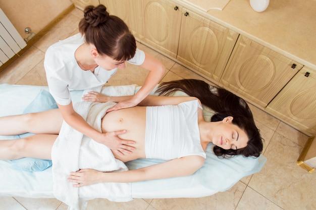 Mooie jonge vrouw arts massagetherapeut in een cosmetologie kamer doen een massage met een zwanger meisje met lang haar. bovenaanzicht