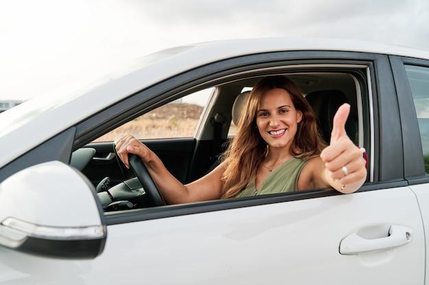 Mooie jonge vrouw autorijden en duimen opdagen uit het raam.