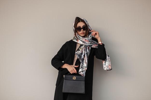 Mooie jonge vrouw bedrijfsmodel met een elegante sjaal op hoofd in modieuze zonnebril in een trendy jas met lederen zwarte handtas staat in de buurt van een vintage muur. sexy luxe meisje. moderne dame.
