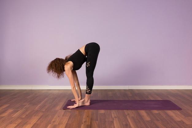 Mooie jonge vrouw beoefenen van yoga binnenshuis