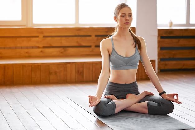 Mooie jonge vrouw beoefenen van yoga in de lotuspositie