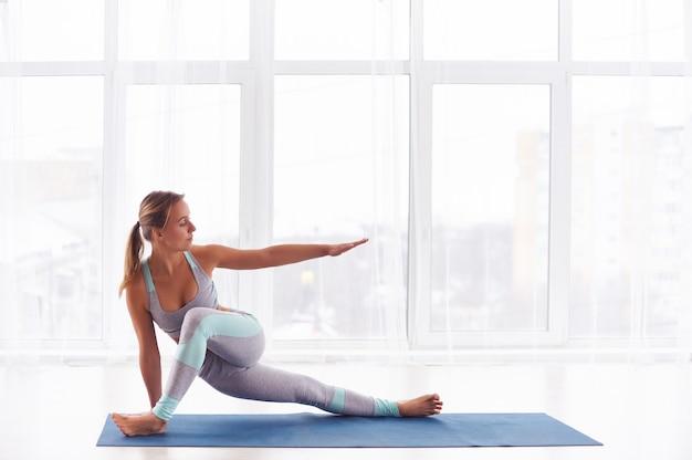 Mooie jonge vrouw beoefent yoga asana in de yogastudio