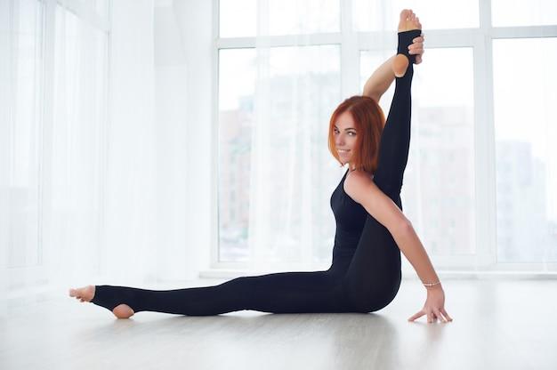 Mooie jonge vrouw beoefent yoga asana parivritta kraunchasana in de yogastudio
