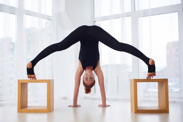 Mooie jonge vrouw beoefent yoga asana prasarita padottanasana in de yogastudio
