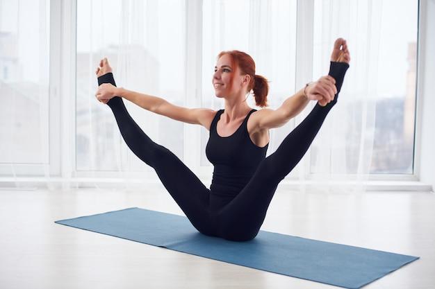 Mooie jonge vrouw beoefent yoga asana urdhva upavistha konasana in de yogastudio