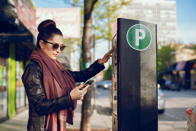 Mooie jonge vrouw betaalt voor parkeren in meter op straat