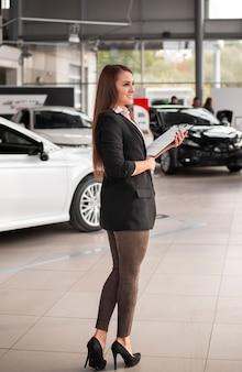 Mooie jonge vrouw bij autodealer