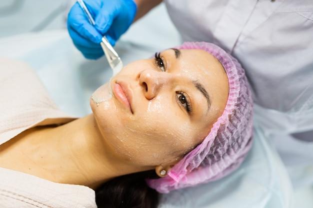 Mooie jonge vrouw bij de receptie van de schoonheidsspecialiste maakt een verjongend gezichtsmasker tegen veroudering