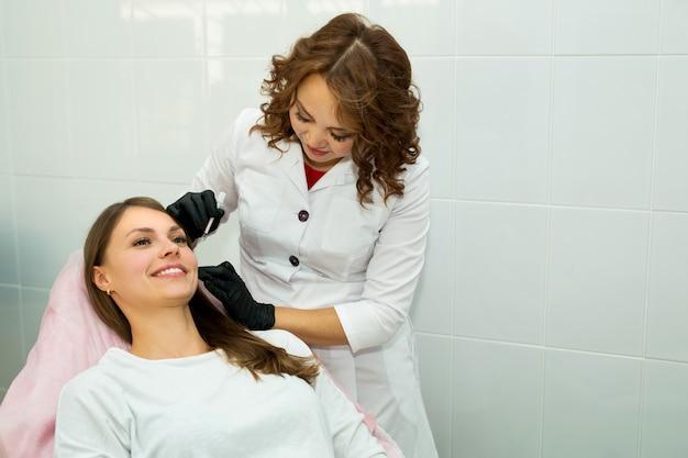 Mooie jonge vrouw bij een receptie bij een schoonheidsspecialiste in een schoonheidssalon