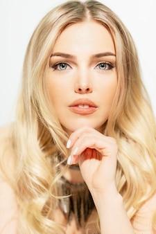 Mooie jonge vrouw, blond, close-up. wit verticaal.