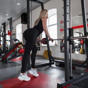 Mooie jonge vrouw blonde in sportkleding met een mooi slank lichaam staat in de buurt van een metalen simulator in een fitness-studio
