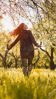 Mooie jonge vrouw buiten. geniet van de natuur. gezond lachend meisje in het voorjaarspark. zonnige dag