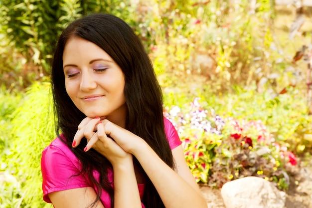 Mooie jonge vrouw buiten in het gras in de zomer