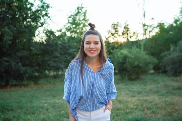 Mooie jonge vrouw buitenshuis. geniet van de natuur. gezond glimlachend meisje in groen gras. gezichts jong mooi meisje, close-up, lang haar